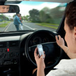 Lady looking at her phone while driving