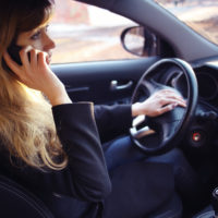 Lady talking on the phone while driving.jpg.crdownload