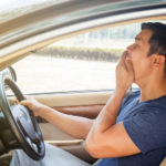 asian man yawning while driving