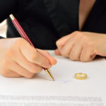 Wife signing divorce agreement with wedding ring on contract