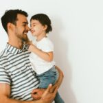 Funny happy dad and daughter play and cuddle together against white background. Good relationship of parent and child. Happy family moments of father and toddler girl. Childhood and parenthood care.