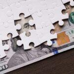 American dollar hidden under puzzle pieces