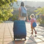 Young mother with daughter arriving at hotel, checking in, carrying luggage.