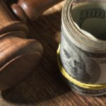 Money roll and judges hammer on wooden table